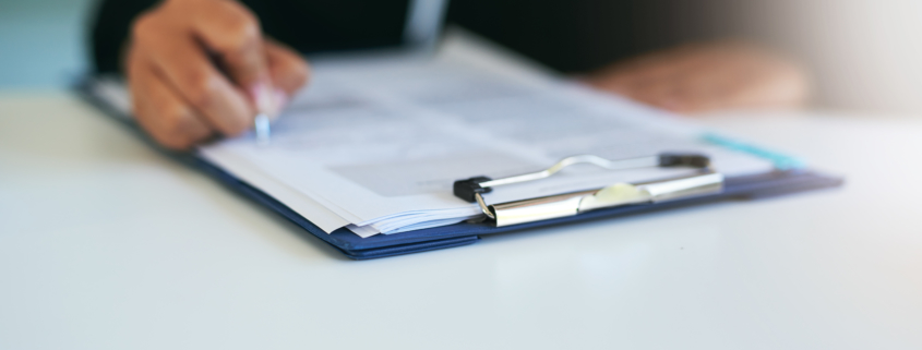 Closeup shot of a woman writing on a piece of paper