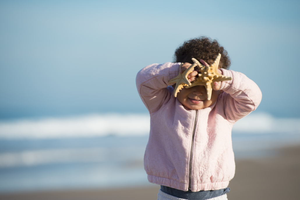 Excited adorable 2 years old girl holding starfish, standing on beach in a sunny day, clear sky on the background.
